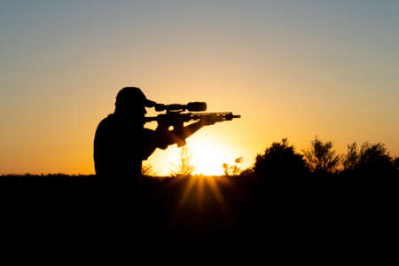 Silhouette of a man with a weapon in his hands on a sunset background