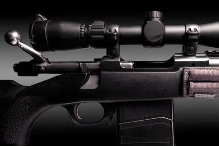 bolt action rifle with riflescope close up on black background, copy space