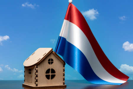 Small wooden house and Netherlands flag, sky on background. Real estate concept, copy space