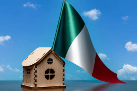 Small wooden house and Italy flag, sky on background. Real estate concept, copy space