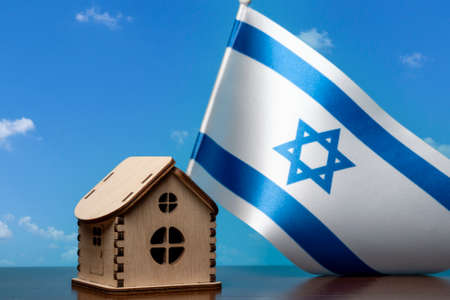 Small wooden house and Israel flag, sky on background. Real estate concept, copy space Zdjęcie Seryjne