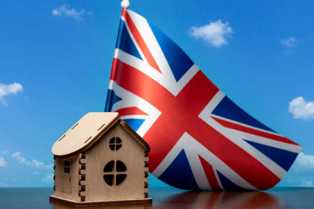 Small wooden house and Great Britain flag, sky on background. Real estate concept, copy space
