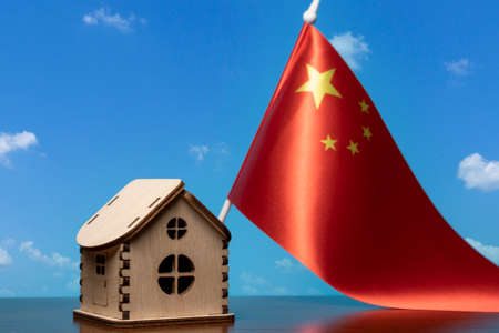 Small wooden house and China flag, sky on background. Real estate concept, copy space