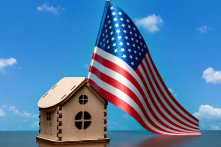 Small wooden house and USA flag, sky on background. Real estate concept, copy space