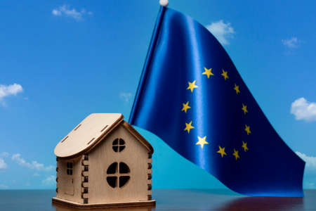 Small wooden house and European Union flag, sky on background. Real estate concept, copy space