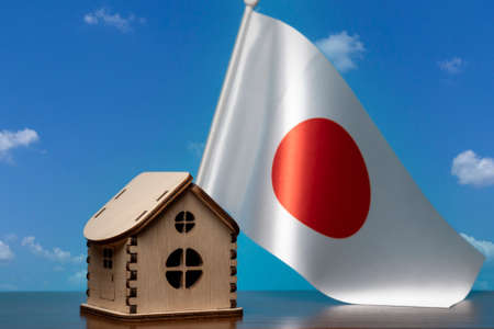 Small wooden house and Japan flag, sky on background. Real estate concept, copy space