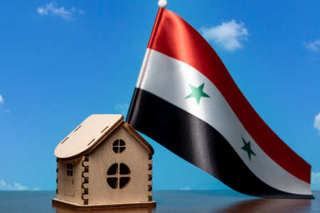 Small wooden house and Syria flag, sky on background. Real estate concept, copy space