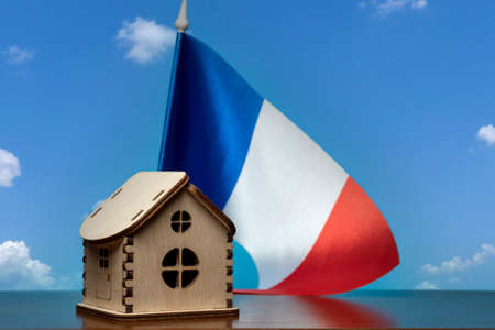 Small wooden house and France flag, sky on background. Real estate concept, copy space