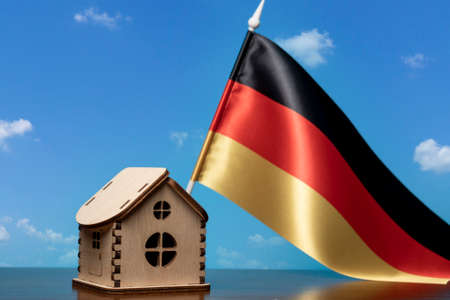Small wooden house and Germany flag, sky on background. Real estate concept, copy space