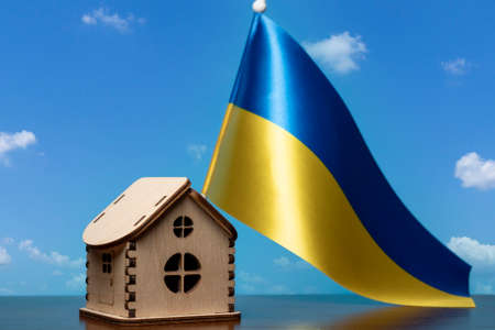 Small wooden house and Ukraine flag, sky on background. Real estate concept, copy space