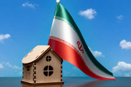 Small wooden house and Iran flag, sky on background. Real estate concept, copy space Zdjęcie Seryjne