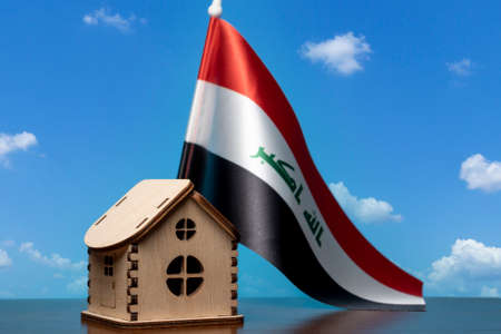 Small wooden house and Iraq flag, sky on background. Real estate concept, copy space Zdjęcie Seryjne