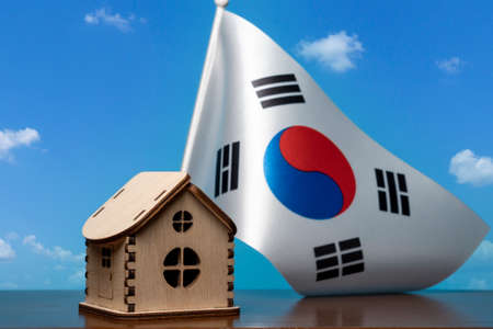 Small wooden house and Republic of Korea flag, sky on background. Real estate concept, copy space