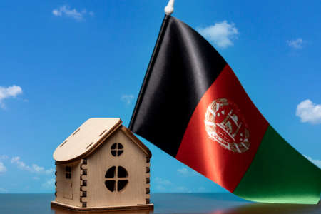 Small wooden house and Afghanistan flag, sky on background. Real estate concept, copy space Zdjęcie Seryjne