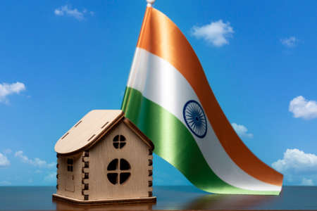 Small wooden house and India flag, sky on background. Real estate concept, copy space