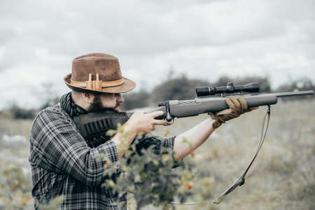 Man shoots a rifle. Bearded man with scout rifle