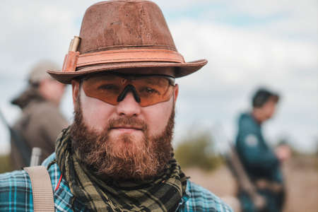 Portrait of a young bearded man in a hat. Bearded man with scout rifle