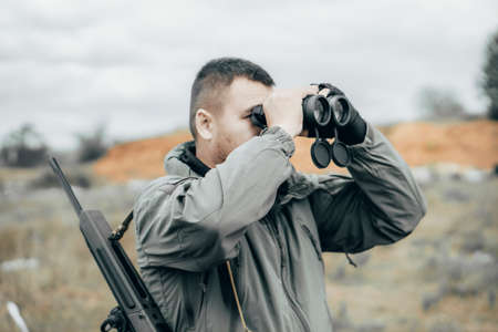 Man with a rifle looking through binoculars. Private military contractor or hunter