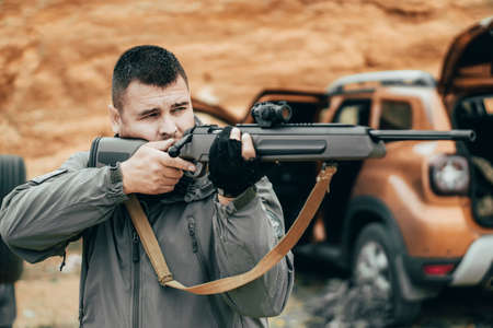 Man shoots a rifle. Private military contractor or hunter