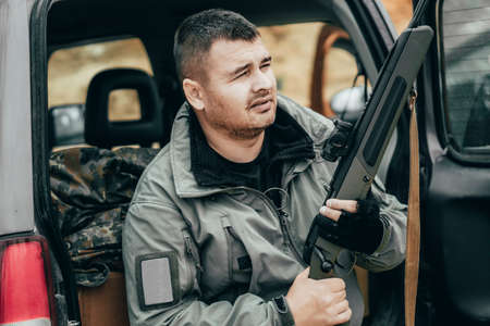 Man with a rifle on the background of the trunk of an off-road car. Private military contractor or hunter Zdjęcie Seryjne