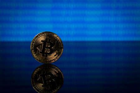 Golden bitcoin, binary code on a blue background