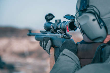Shooter with a rifle. Man shoots a rifle, rear view, selective focus on optical sight, close-up