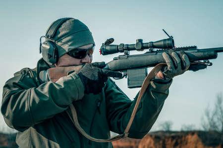 Portrait of a shooter with a rifle. European shoots a rifle with a optics sight Zdjęcie Seryjne