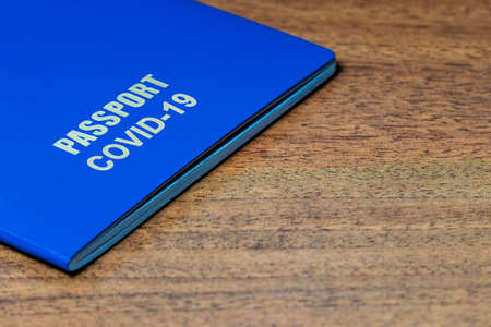 Blue passport with note COVID-19 on the desk. Travel and coronavirus concept