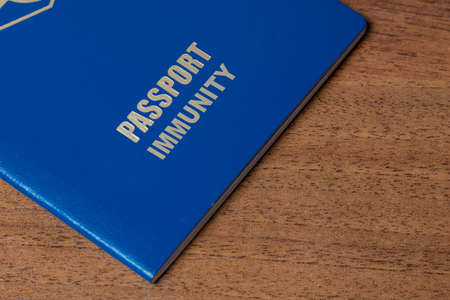Blue passport with note Immunity on the desk. Travel and concept Zdjęcie Seryjne