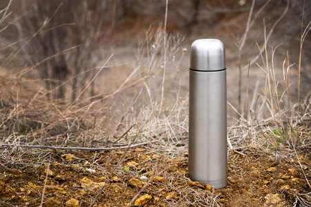 Steel vacuum flask  with tea or coffee, outdoor. Hiking, active tourism, picnic, hot drink concept