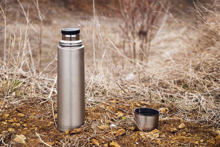 Steel vacuum flask with tea or coffee, outdoor. Hiking, active tourism, picnic, hot drink concept Zdjęcie Seryjne
