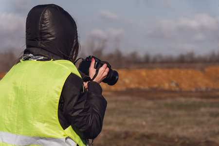 Girl photographer in a yellow rescue vest with a camera in her hands. Back view, no face, copy space Zdjęcie Seryjne