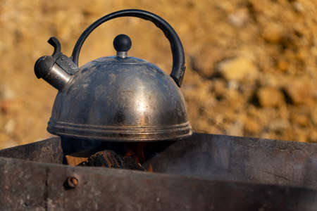 Old metal kettle on the grill, close-up