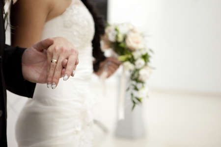 The Bride and groom hold each others hands.
