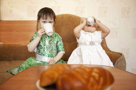 The children were sitting at the table drinking tea. Stock Photo