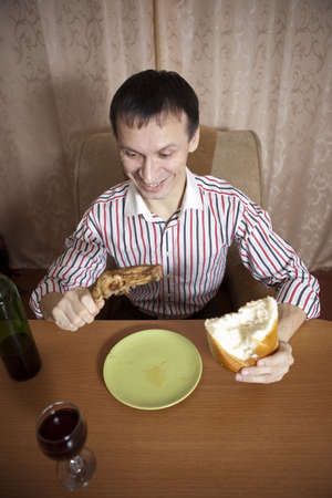 The young man eats at the table Stock Photo - 17567353