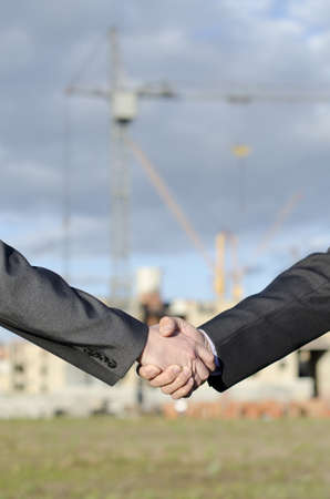 Hand shake against real estate building