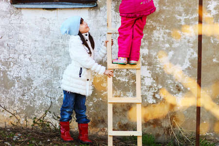 help: Children help each other to climb the ladder.
