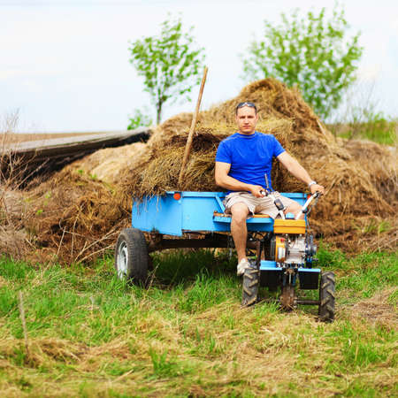 cultivator: The man carries hay on a cart. Stock Photo