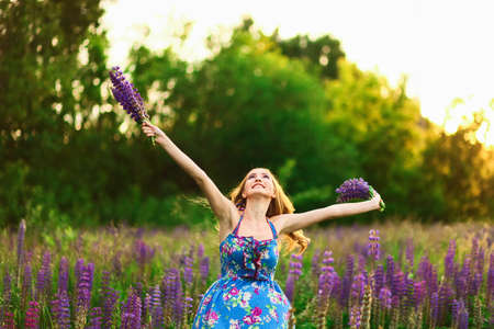 lupins: Beautiful young girl in the colours of the lupins. Stock Photo