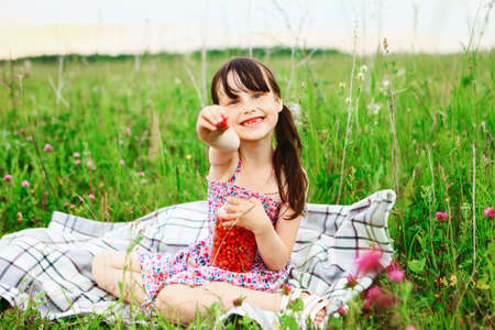 The Little girl picking and eating strawberries. Stock Photo