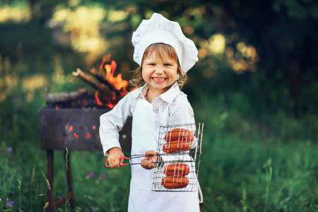 The Children preparing sausages on the coals. Stock Photo