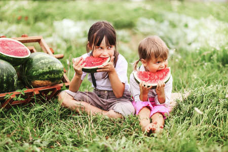 The Little girl eating watermelon a outdoors.