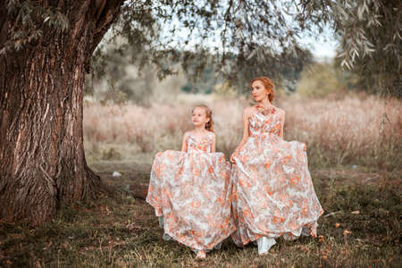 The Mother and daughter in matching dresses.