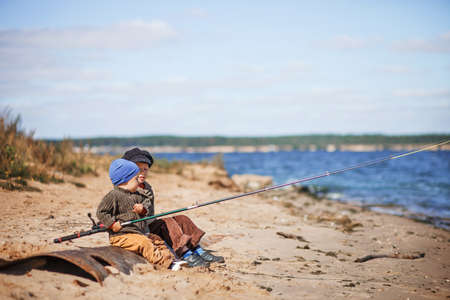 The Small children fishing on the river. Stock Photo