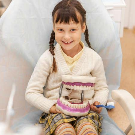 Little girl treats teeth at the dentist.