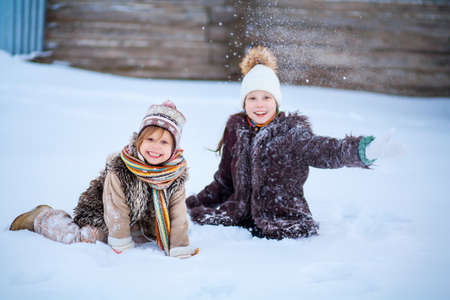 The Little girls playing with snow in winter. Stock Photo