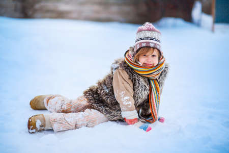The girl playing with snow in winter.