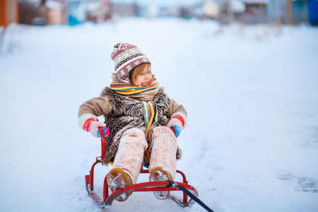 Portrait of a little girl with a sleigh.