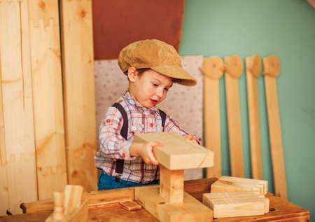 De jongen die in een timmerwerkplaats werkt.
